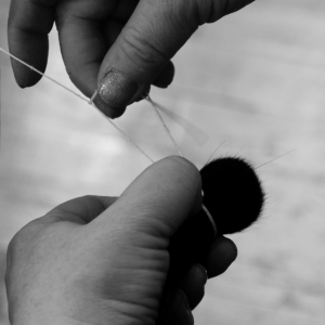 Traditional production of a brushes head. After shaping, the hairs are being tied together.