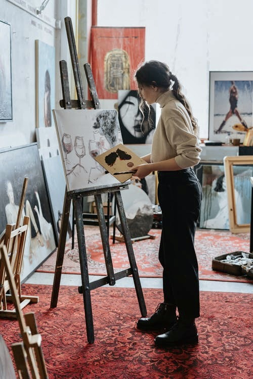 Woman painting a picture with an artists brush