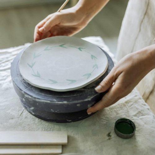 Frau bemalt Keramik mit Keramikfarben und Pinsel