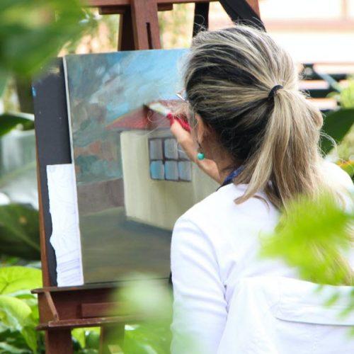 Frau malt im Freien ein Bild mit Acrylfarben und Pinsel