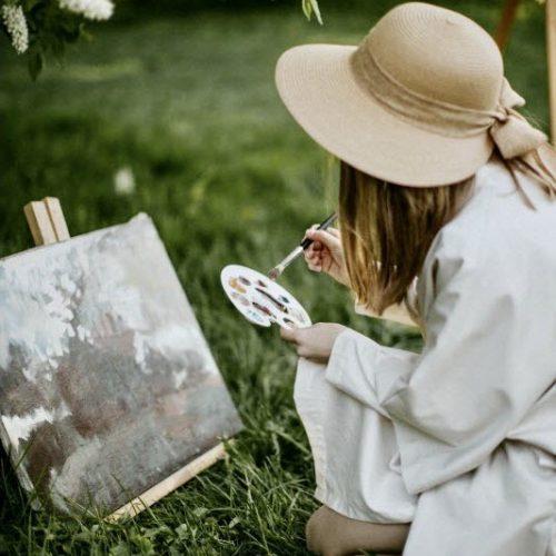 Frau mal im Freien ein Gemälde mit Ölfarben und Künstlerpinsel