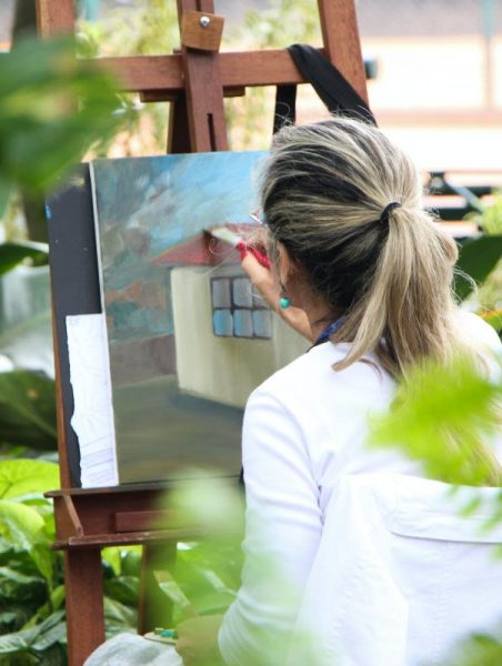 woman painting with acrylic colors and an artist brush