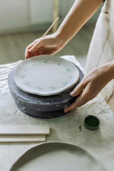 woman painting a ceramic plate with ceramic colors and an artist brush