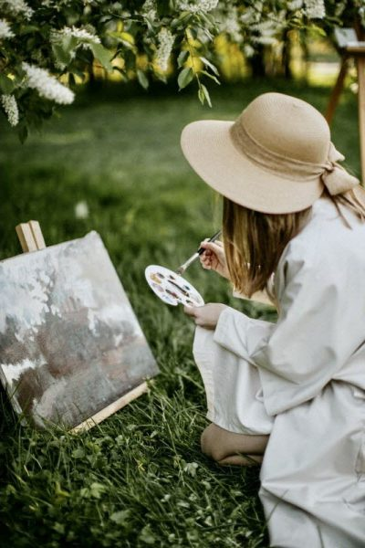 woman painting with a artist brush and oil colors